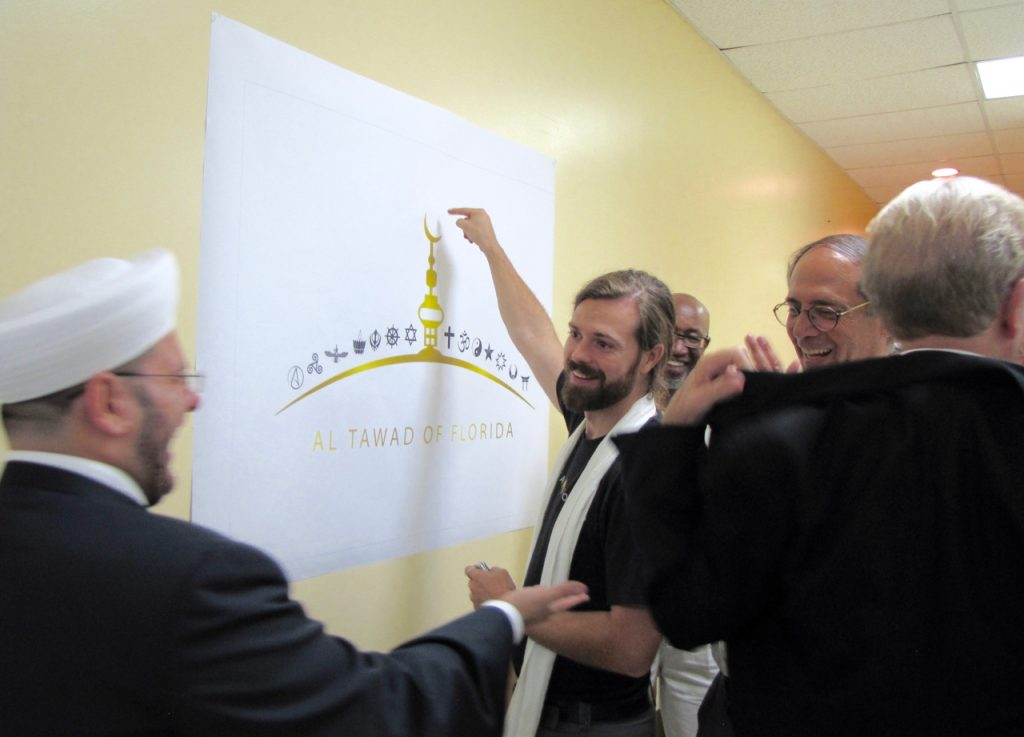 Imam Zaher Badaraany, Rev. Chris Miller, and Ted Brownstein work together to name all of the religions represented on the banner